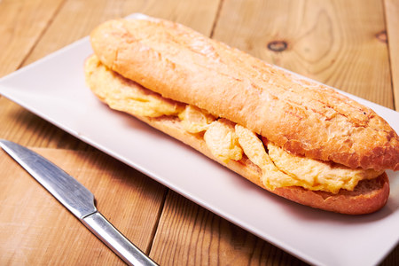 Close-up of tasty sandwich made of crispy baguette and omelette on wooden background. Standard-Bild