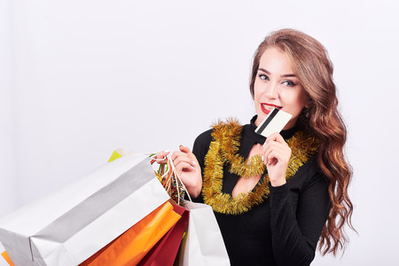 Portrait of a young happy elegant woman with colorful shopping bags in hands and biting credit card isolated on white background. Christmas discounts and black friday concept. Foto de archivo