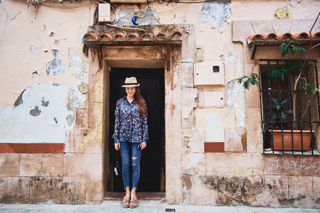 Beautiful young happy woman in a doorway of an old building. Travelling and tourism concept. Stock fotó