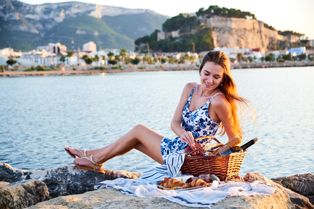 Picnic on the beach. Young woman sitting with basket of food on sunny summer day. Sea and castle on background.
