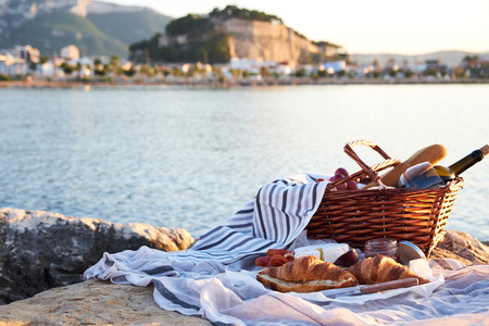 Romatic picnic on the beach in Denia, Spain. Picnic basket with red wine, bread, jam, cheese and jamon on a sunny day with sea and castle on background. Stockfoto