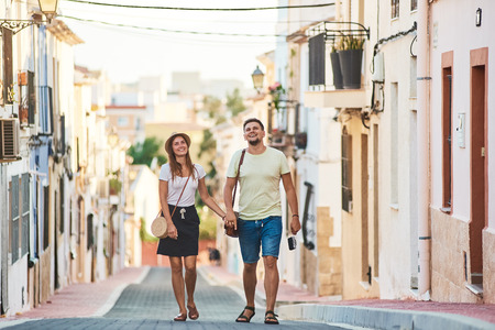 Young happy couple walking holding each others hand in Spanish town Denia. Stylish man and woman on vacations in Spain, Europe. Tourism and travelling concept.