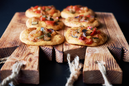 Many freshly baked mini pizzas сocas on wooden board. Traditional Spanish pastry with vegetables.