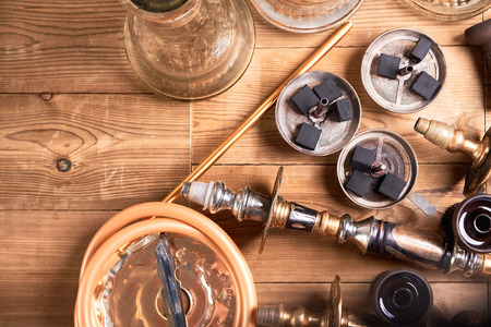 Top view of shisha details and coal on wooden background. Hookah smoking concept. Copy space. Banco de Imagens