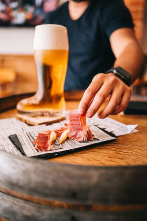 Beer glass boot with delicious spanish iberian ham snacks on a wooden barrel Zdjęcie Seryjne