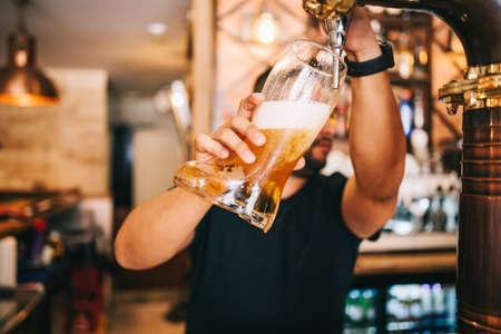 Bartender draft beer in tap in beer glass boot. Zdjęcie Seryjne