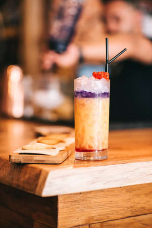 Beautiful alcoholic cocktails on wooden bar counter and cheese snack