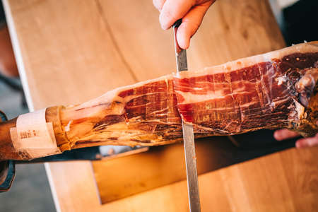 A man's hands in a restaurant are cutting a slice of traditionally Spanish Iberian ham. Close-up meat. Zdjęcie Seryjne
