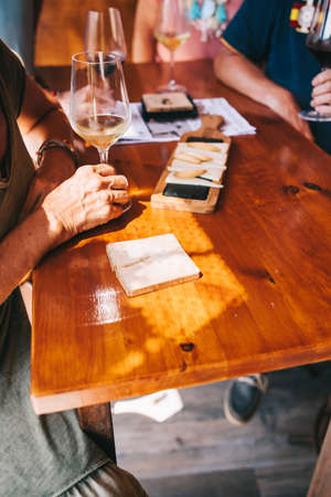 People eat cheese and drink wine in a terrace restaurant on a sunny day. A table in a restaurant with a cheese plate, bread, white wine snacks full of visitors.