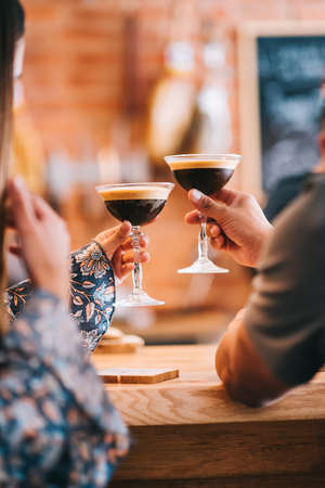 couple holding glass with espresso martini cocktail, decorated with coffee bean. Smooth image with shallow depth of field. Zdjęcie Seryjne