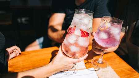 Group of friends sitting on a summer terrace with cocktails in hand and snacks on the table