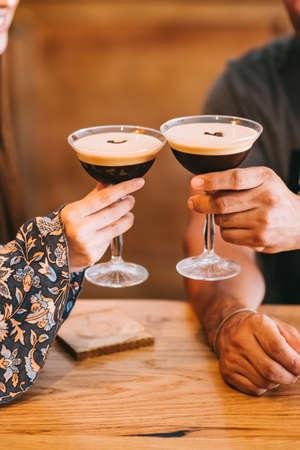 couple holding glass with espresso martini cocktail, decorated with coffee bean. Zdjęcie Seryjne