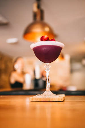 Exquisite maroon cocktail in a special glass on a wooden bar counter against the background of a bar Zdjęcie Seryjne