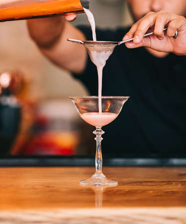 Male bartender pouring a delicious cocktail from the steel shaker through the sieve to a glass on the bar counter in the dark blurred background