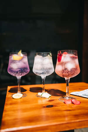 Beautiful line of multi-colored alcoholic cocktails at a party on the martini table, vodka in large glasses