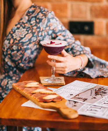 Exquisite burgundy-red cocktail in a special glass on a wooden bar counter against the background of a bar counter