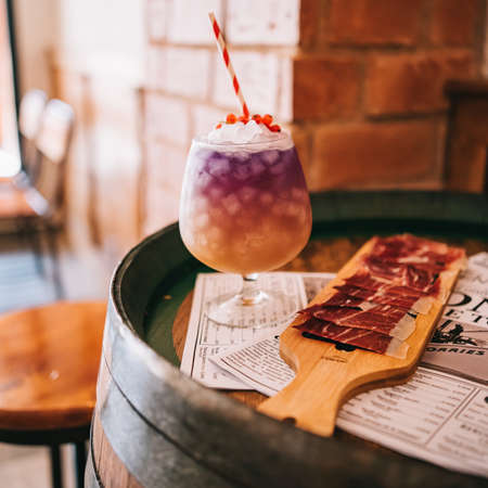 Beautiful alcoholic cocktails on a wooden barrel with a spanish ham
