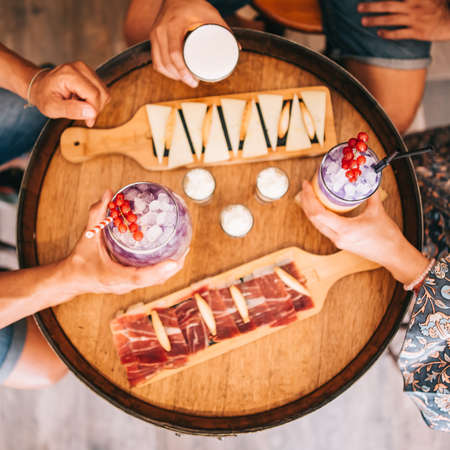 a group of friends sits on the terrace in the summer behind a wooden barrel with cocktails and a snack. Top view