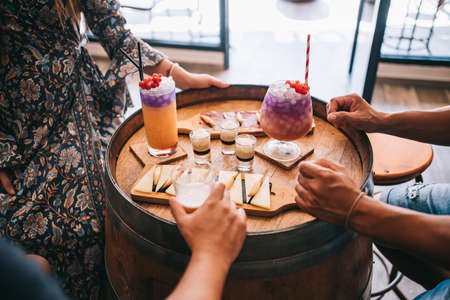 a group of friends sits on the terrace in the summer behind a wooden barrel with cocktails and a snack