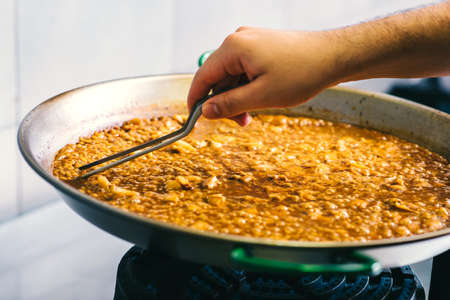 Cooking paella chef checks readiness with tweezers - Spanish food