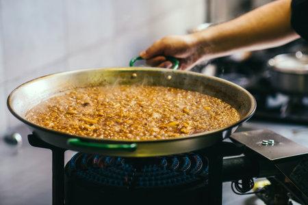 Cooking paella, chef turning paella - Spanish food