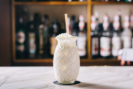 White Russian at the bar on a blurred background of alcohol. Party at a nightclub for adults. Milkshake with cream, vodka and lemon Zdjęcie Seryjne
