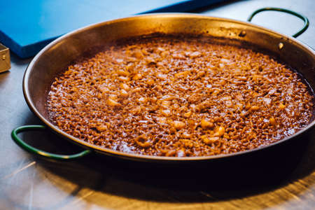 Cooking paella in large pot - Spanish food