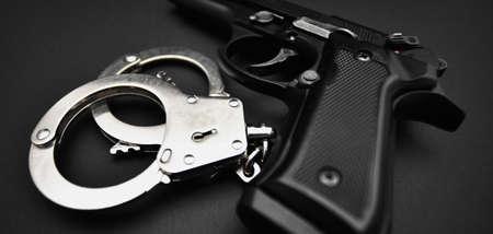 Gun and Handcuffs close-up Stock Photo