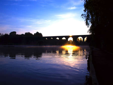 Viaduct Bridge over Misty Lake at Dawn Sunset