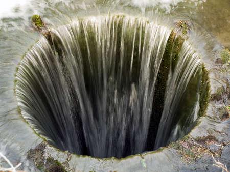 drenaggio: Profondo pozzo senza fondo con l'acqua che scorre nelle