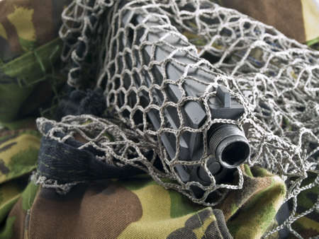 concealed: Black Pistol Through Military Net with Camouflage Stock Photo