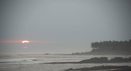 big sun peaking thought the clouds at Pererenan Beach bali at su Banco de Imagens