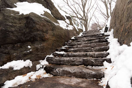 Snow and ice gathered on stone stairs in Central Park, New York City Фото со стока
