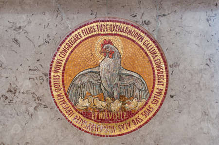 Detail of mosaic in church including a chicken with chicks and bible verse Фото со стока