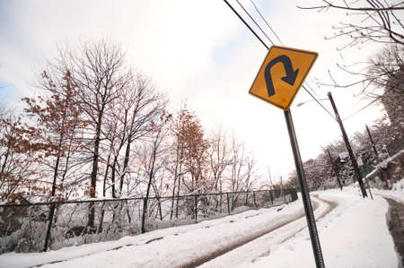 U-turn sign on snowy road in urban area during winter