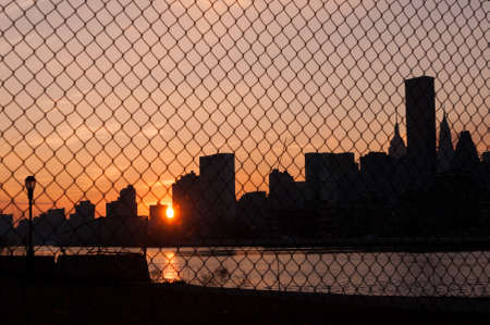Sun sets over New York City through a chainlink fence Фото со стока