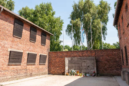 Memorial at Auschwitz between buildings with flowers Редакционное