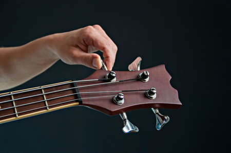 tuning: Tuning acoustic bass on a black background