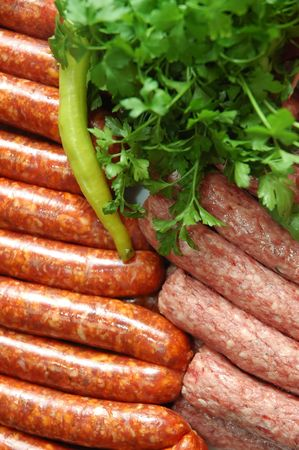 uncooked bacon: Fresh sausage and mixed grill prepared for bbq and decorated with parsley and paprika