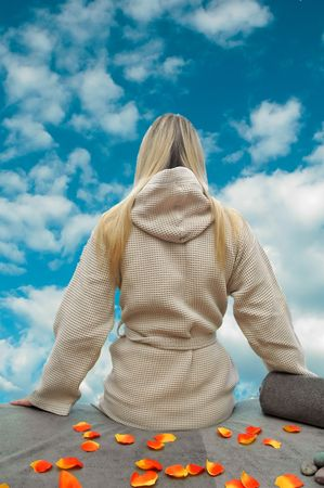 Girl relaxing after massage and looking in blu sky with clouds. photo