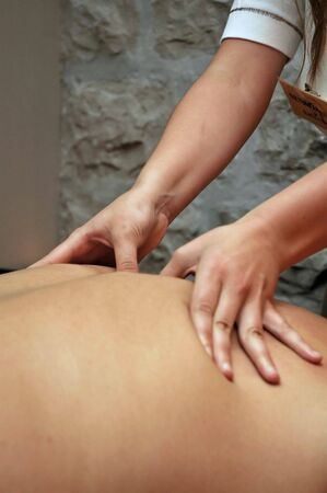Massage detail with womans hand on mans back.