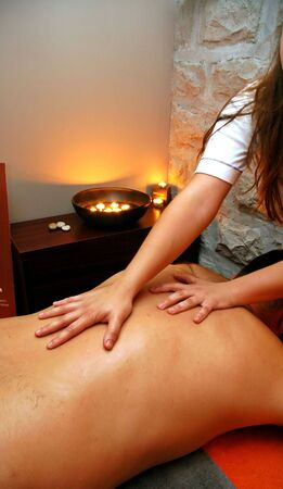 Part of exotic interior of massage room with woman hands on mans back in foreground.