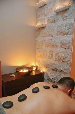 Hot stone massage treatment in spa center.