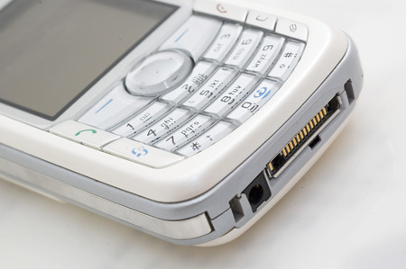 wireles: White mobile phone. Close up view on keyboard.