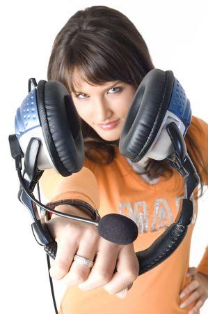 Beautiful brunette girl with headphones listening music and playing. Nice orange shirt. Stock Photo