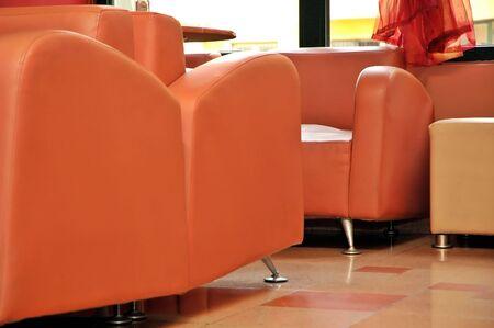 Interior of modern restaurant. Orange leather and luxury chairs.
