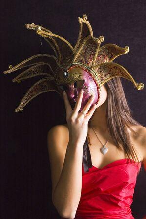 carnaval venise: Jeune fille brune en rouge avec masque carnaval de Venise sur fond noir.  Banque d'images
