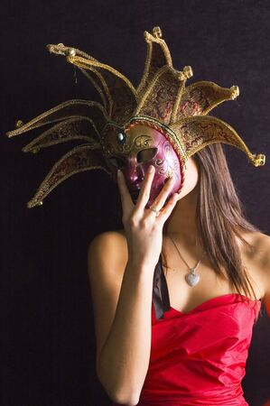 Young brunette girl in red with Venice carnival mask on black background. Stock Photo