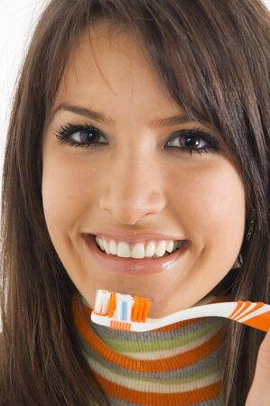 Young brunette girl with tooth brush in hand. Concept of tooth care and oral hygiene.