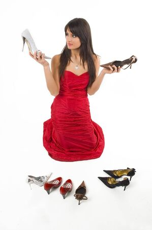 exasperation: Young brunette girl with dificult choice.Many shoes and only one is good.